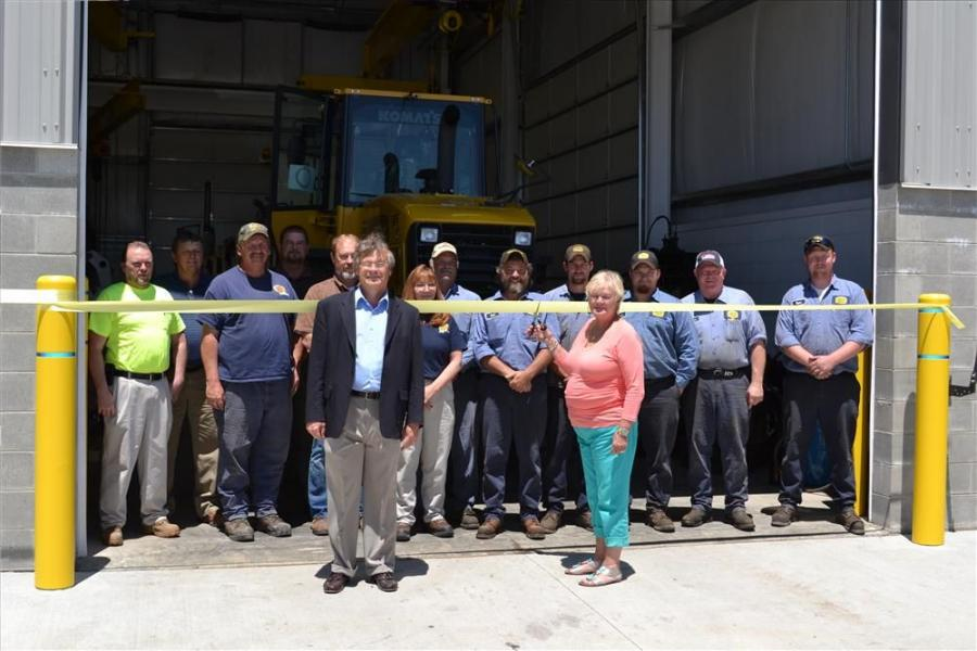 Richard Early (L), CEO, and Cookie Stivison prepare to cut the ribbon with the Piketon team behind them.