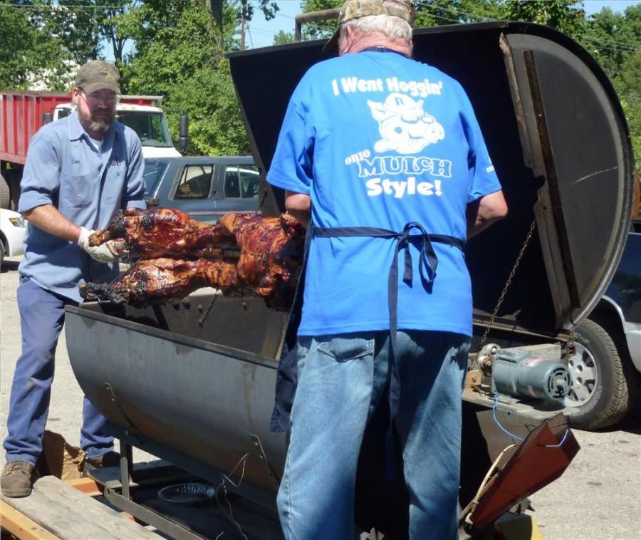 """""""Pig Roast Master"""" Bob Schleppi (L) and RECO Equipment Service Manager Dan Wetzel remove the pig from the custom roaster."""