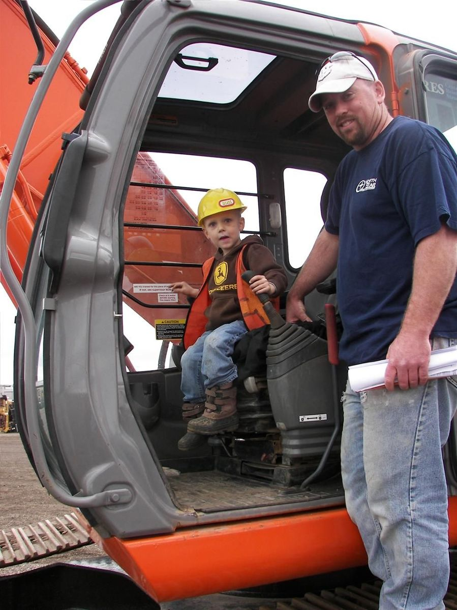 Mason Hinchley gets a feel for what it's like behind the controls of this Hitachi Zaxis 230LC excavator as his proud father Matt Hinchley of Hinco, Rochester, Minn., looks on.