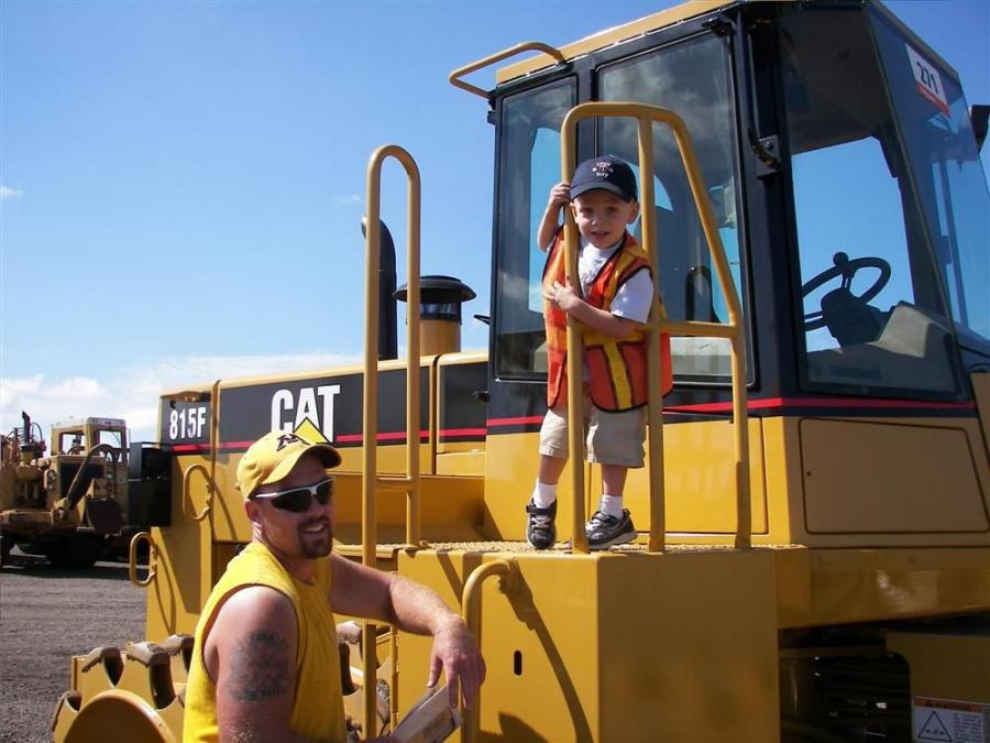 Matt Hinchley, with his son Mason, from Hinco of Rochester, Minn., look at concrete equipment and skid steers like this Cat 815F compactor.