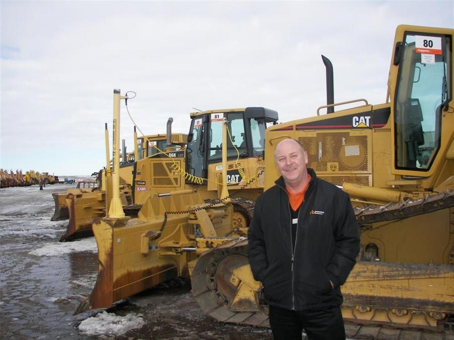 Ritchie Bros.' D. Nick Nicolson, senior vice president, Central U.S. and Latin America, stands with a D6 Cat dozer.