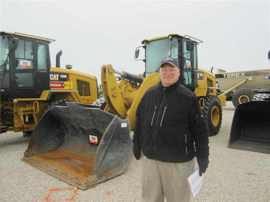 Bill Farmer, Construction Equipment Sales Co., looks over the Cat wheel loaders.
