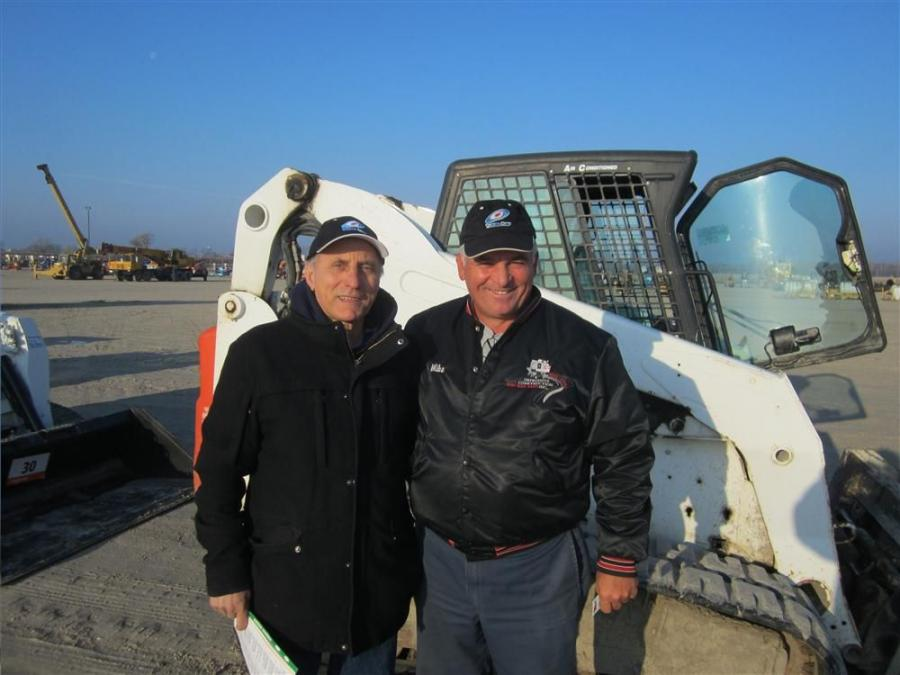Andy Maino (L) and Michael D'Alesio of Impressive Construction Inc. look over the Bobcat skid steers.