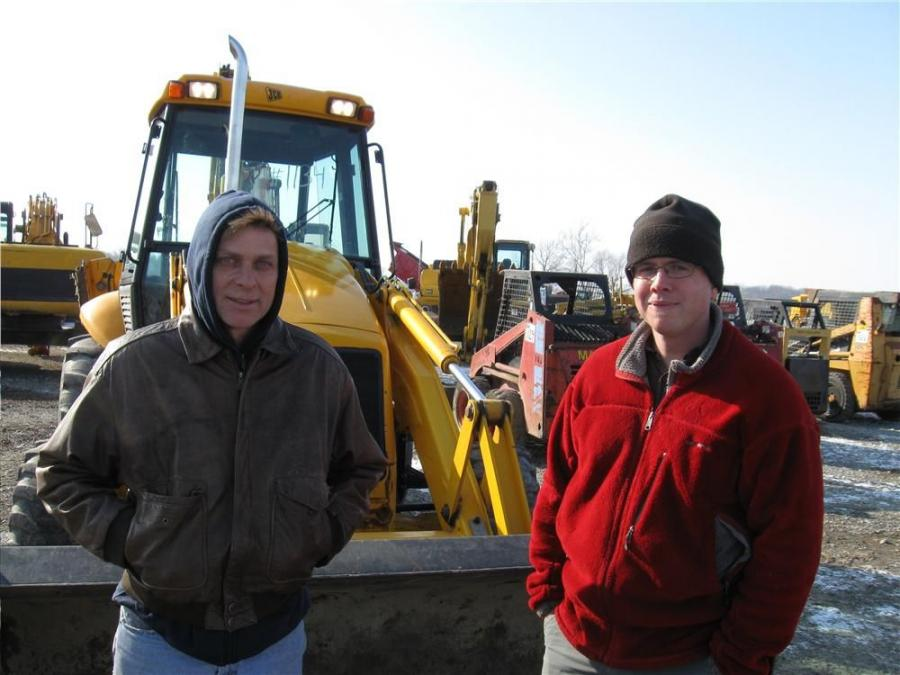Robert Tomey (L) and Tom Henderson of Henderson Construction considers bidding bid on this JCB 214e backhoe.