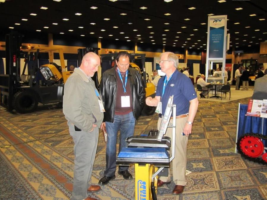 Barry Stoughton (R), president, BLS Enterprises, shows his track pads to Bill Lyon (L) and Rick Albert, president, Rick Albert Machinery, Pleasanton, Calif.
