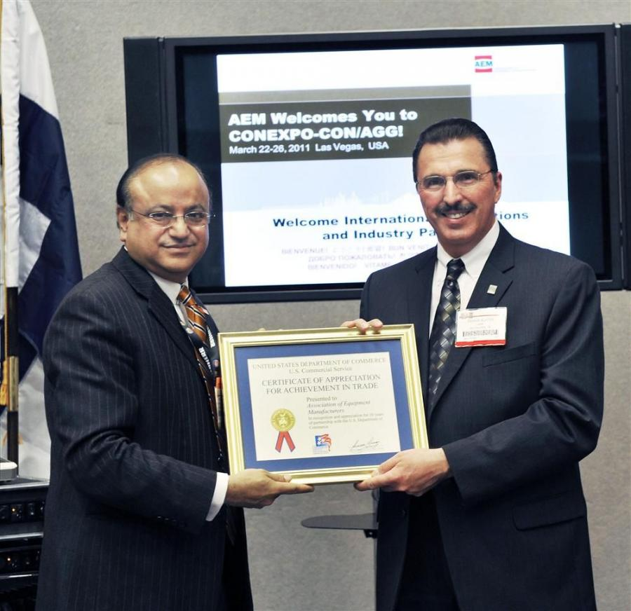 "AEM President Dennis Slater (R) accepts a U.S. Commerce Department ""trade achievement award"" from Suresh Kumar, assistant secretary of commerce for trade promotion and director general of the U.S. and Foreign Commercial Service."