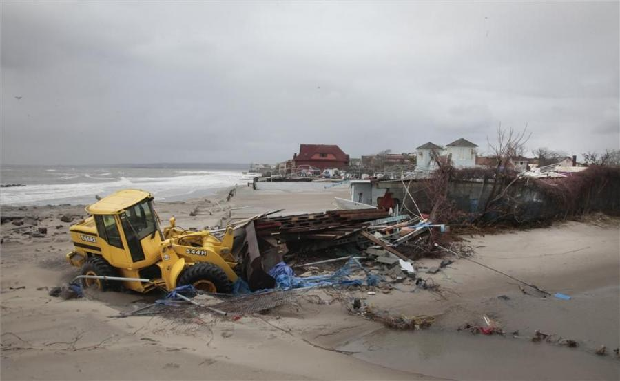 A John Deere wheel loader clears debris caught in floods and washed onto the beach near the Seaview community in the aftermath of Superstorm Sandy on Oct. 30, in Coney Island, N.Y.