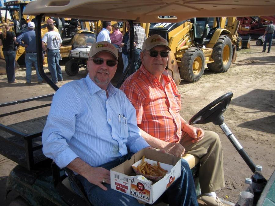 Taking in the auction via golf cart are Mark Hockaday (L), president of Henry Manufacturing, and Henry Branscome, founder of Henry Manufacturing, Williamsburg, Va.