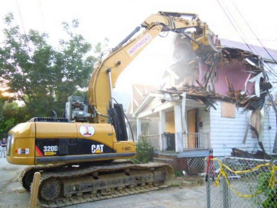 The crowd of onlookers cheered on the demo crew as its Caterpillar 320 excavator made its first swipes at the roof of the house. As the debris fell to the basement, church bells rung out.