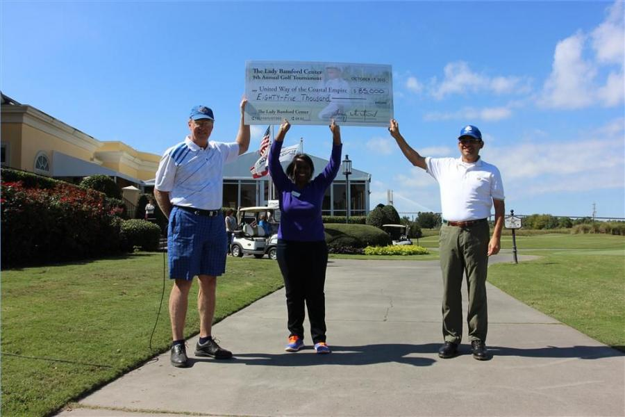 (L-R): Tony Whitehurst, tournament champion and JCB finance director; Tammy Mixon, executive director of Wesley Community Centers; and Arjun Mirdha, president and CEO of JCB North America, celebrate the $85,000 raised by the 2015 tournament.
