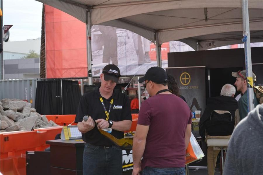 "Casey Reed (L) takes a break from ""emceeing"" the crushing demos to explain specific features to an interested customer at the World of Concrete show.  Reed is MB Crusher America's director of sales."