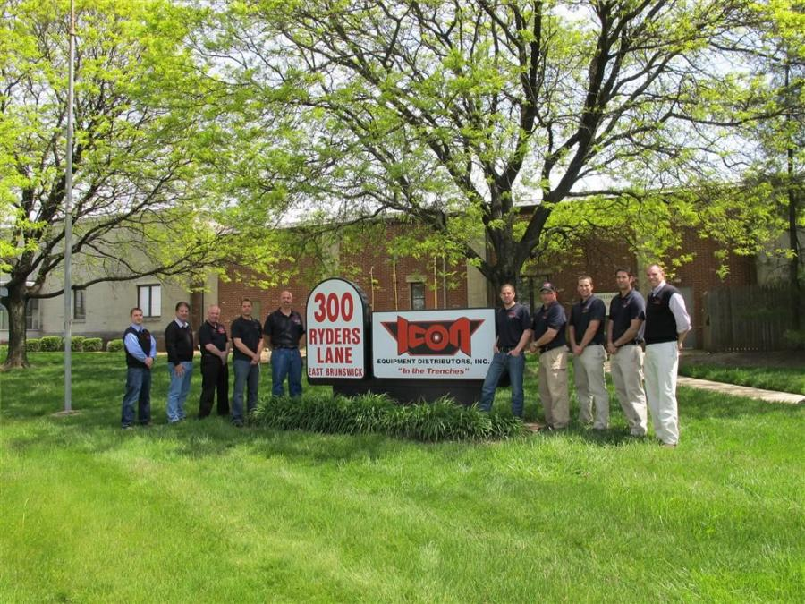 Company employees flank the company sign.