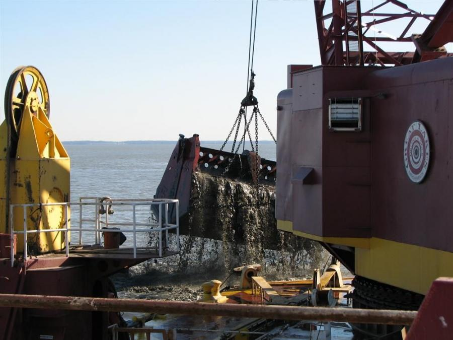 Stacy Ouellette/U.S. Army Corps of Engineers photo. A clamshell bucket dredge scoops dredged materials from the Chesapeake Bay for transport to Poplar Island.