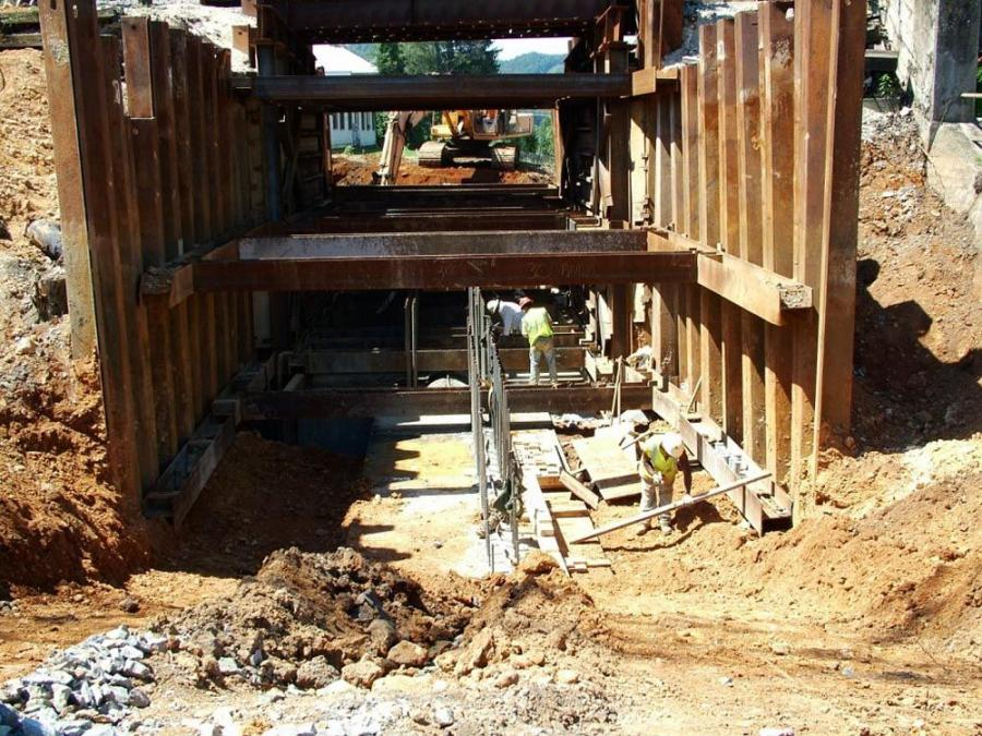 Workers build abutment B under a temporary span.