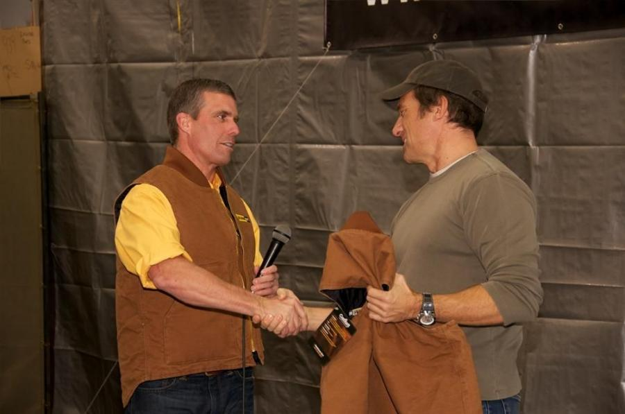 Jamie Alban (L), president and owner of Alban CAT, introduces Mike Rowe and presents him with an Alban vest.
