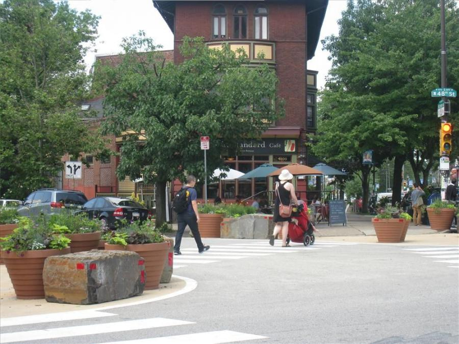 Protected by a buffer of rustic blocks of salvaged Pennsylvania Bluestone and lushly planted large terra-cotta style planters, these bump-outs create a new safe space for pedestrians waiting to cross the intersection.