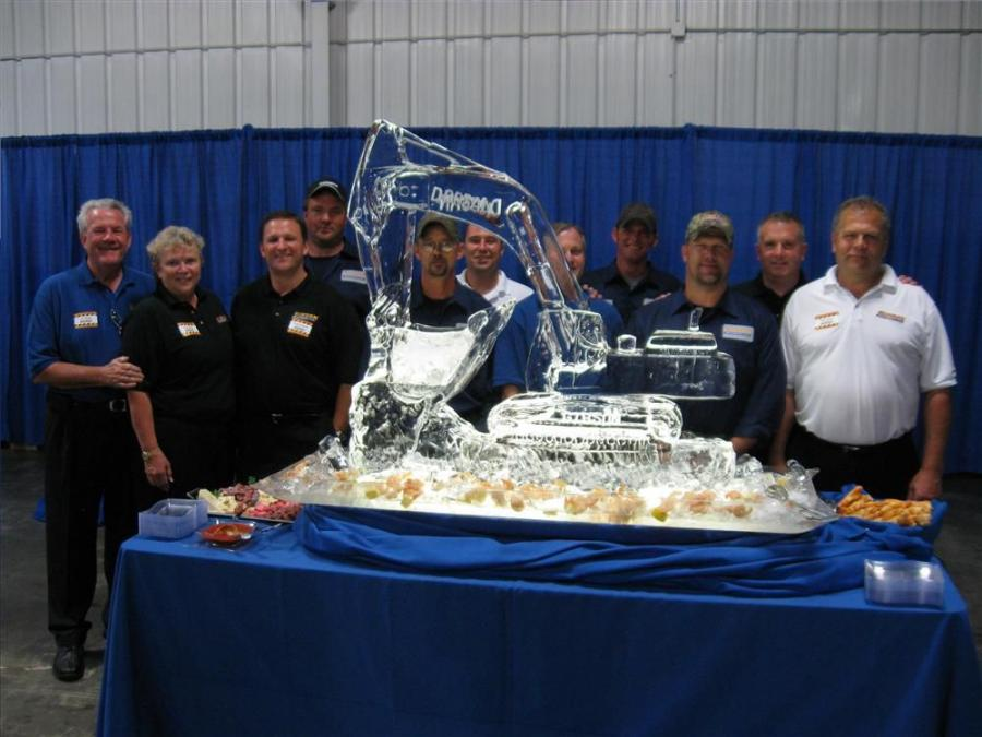 The Gibson Machinery crew gets ready for their grand opening celebration behind an ice carving in the shape of a Doosan excavator.