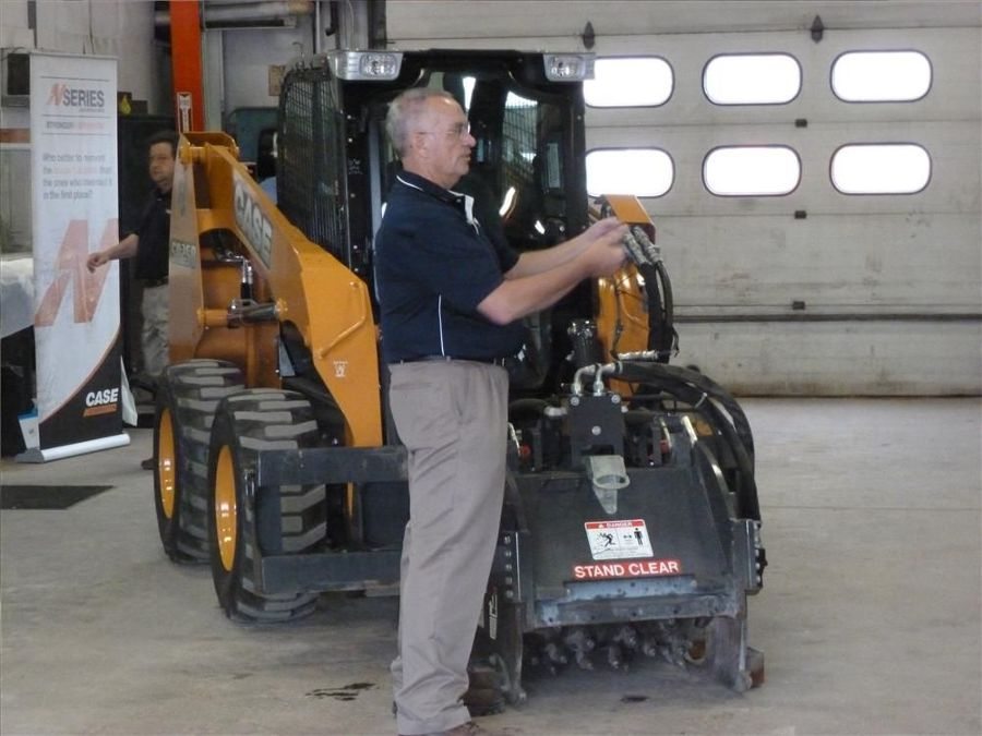 Jim Fox, Case Construction product specialist, points out the features on a Case skid steer with milling attachment.