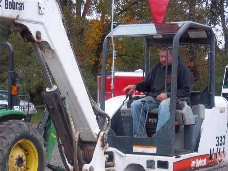 Pat Bruno of Patsy Bruno & Son, Huntington, Staten Island, N.Y., checks the controls on a Bobcat 337 mini-excavator.