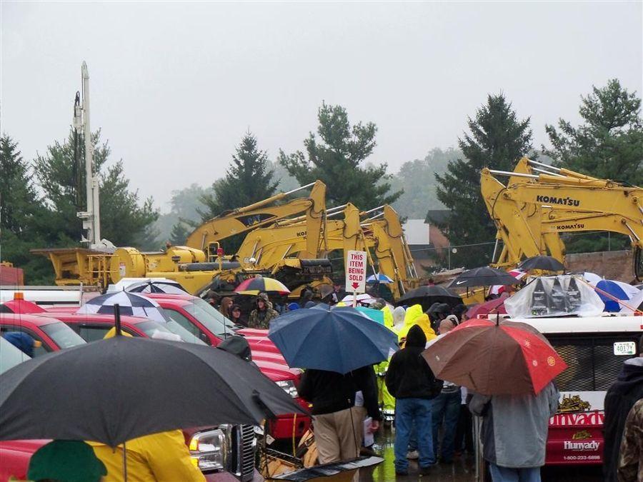 Many contractors attended the auction despite heavy rain. Here, bidders head over to the heavier iron up for sale.