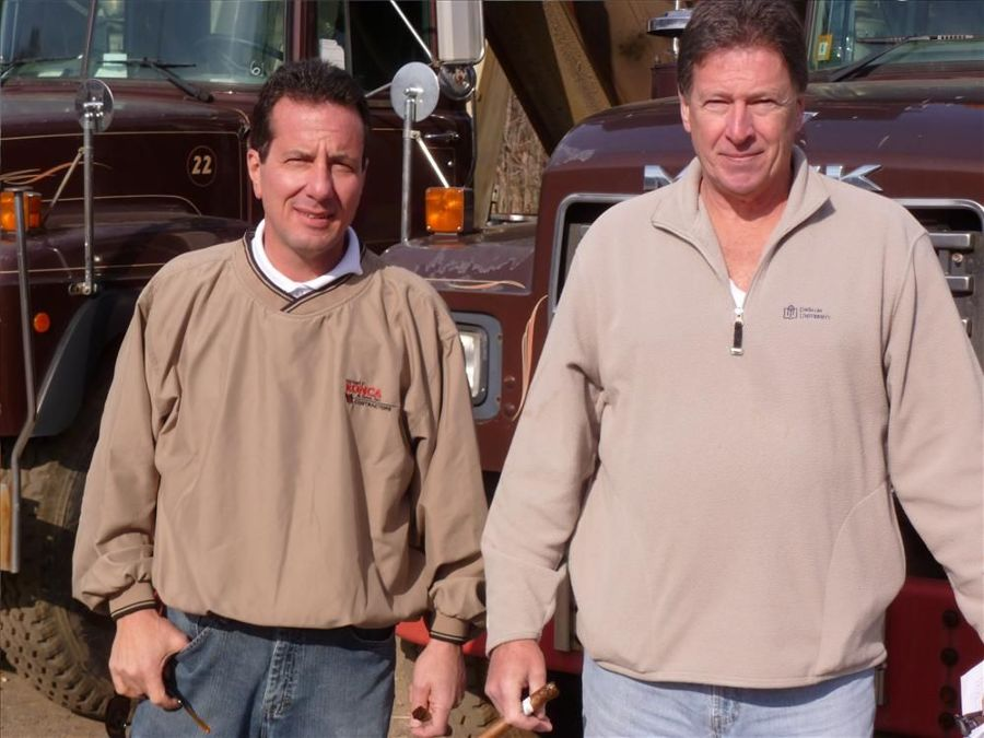 Fred Ronca (L) of Michael F. Ronca & Sons Contracting Inc., Bethlehem, Pa., and Kenny McCusker look over the Mack dump trucks.
