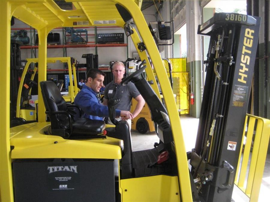 William Turrell of Alex & Ani (R) looks over the equipment with a JCB employee.