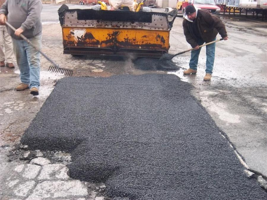 Professional crews repair a hole with material from the RoadMixer.