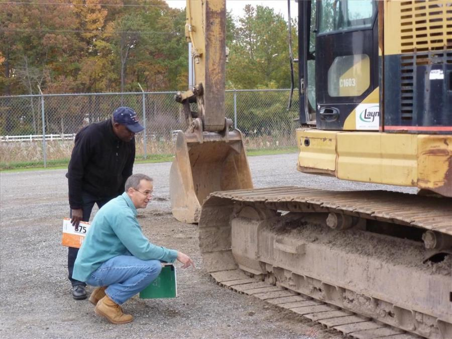 Prince Baffour-Osei (L) of PBO Associates International Brokers and Chuck Coe of Ribco, East Stroudsburg, Pa., look over a Caterpillar 321C excavator.