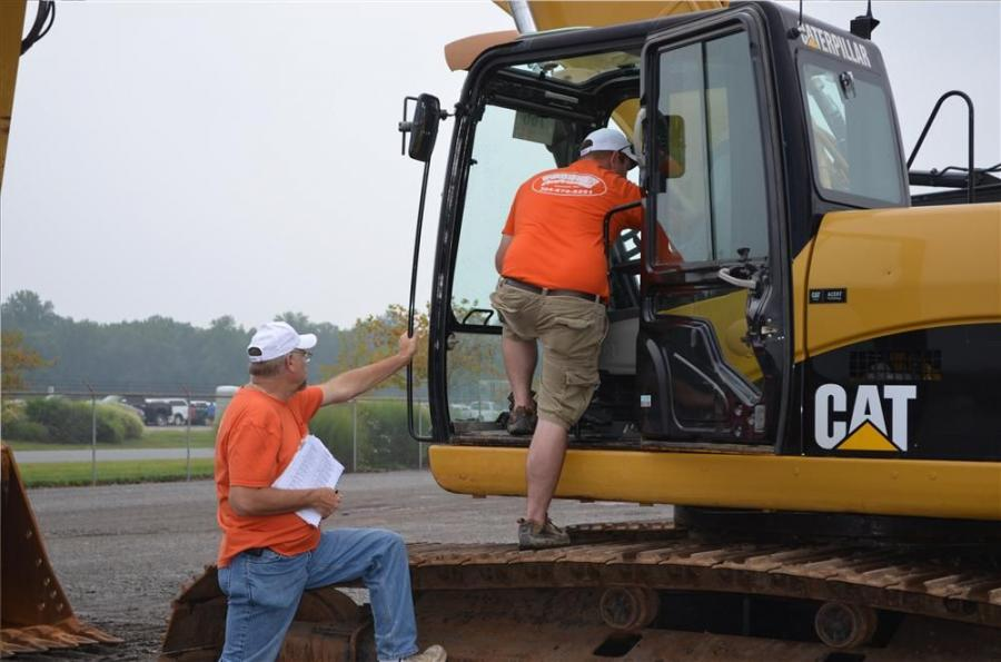 Don Forquer (L), owner of Forquer Contracting located in Maidesville, W.Va., and Jody Forquer look over a Caterpillar excavator.