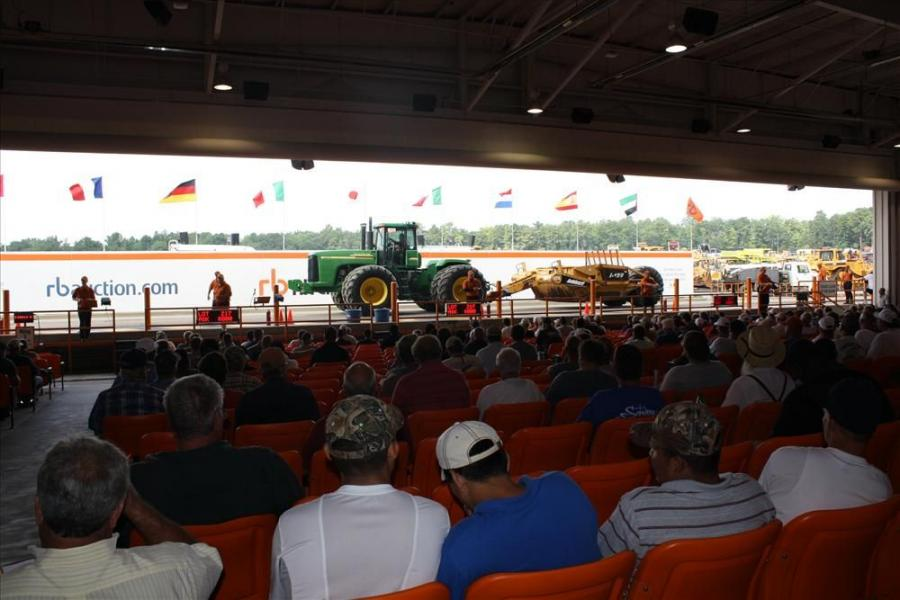 Bidders watch as the iron rolls past on the ramp during the Ritchie Bros. Aug. 28th auction in North East, Md.