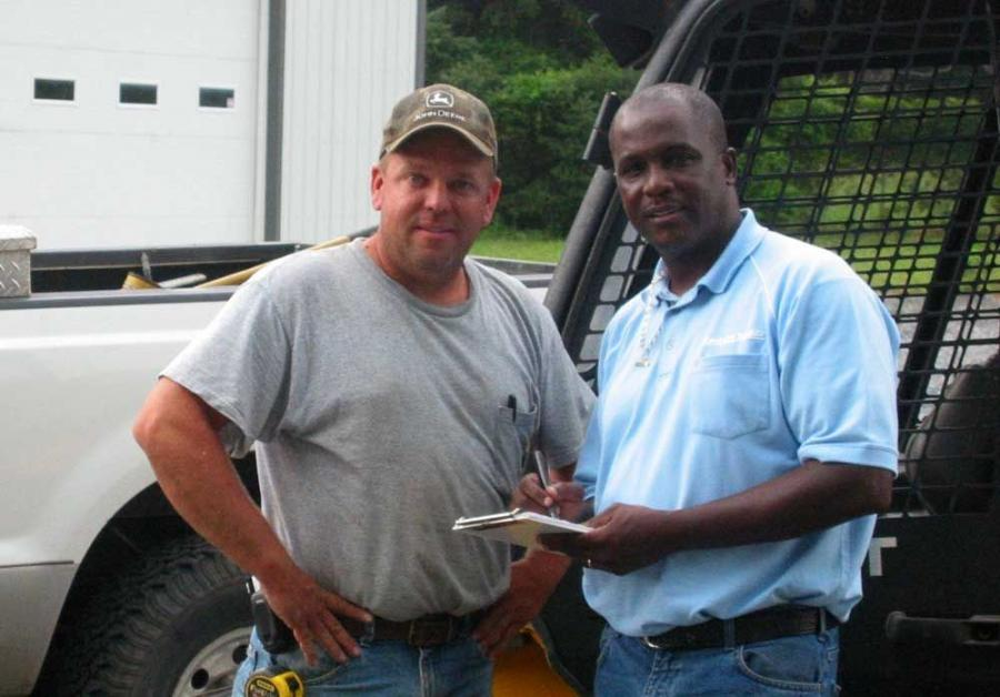 Al Stewart (R), sole operator/employee of Stewart's Parts and Services, Newark, Del., discusses parts options with Michael Hitchner of Michael Hitchner's Hauling and Excavating.