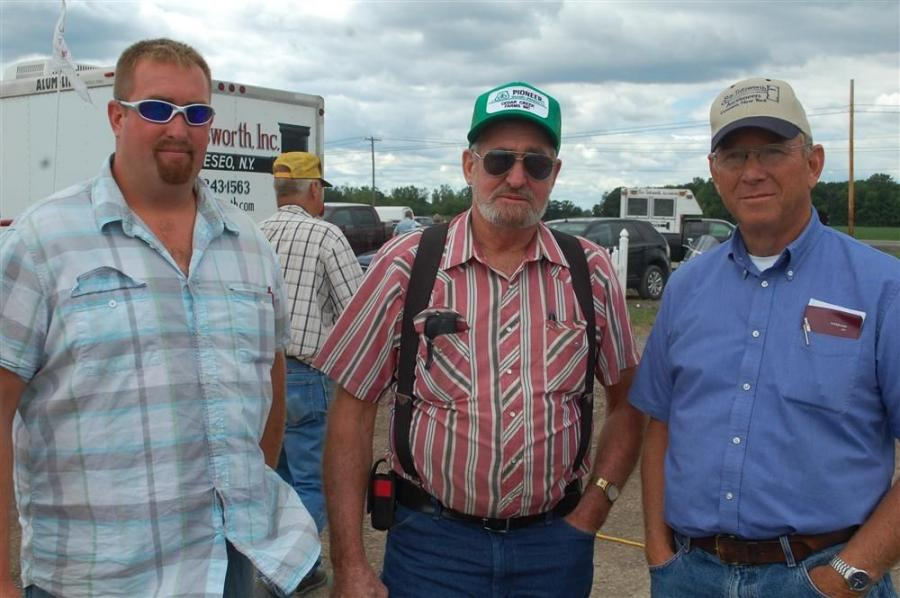 (L-R): Bill Lunkenheimer and Chuck Lunkenheimer of Cedar Creek Farms, Cato, N.Y., discuss the condition of a Caterpillar loader for sale with Roy Teitsworth before the start of the event.