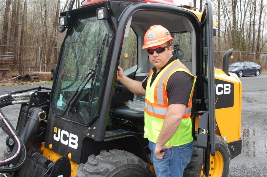 James Slaughter, division equipment manager of Tilcon New York, inspects the side door entry and spacious cab of the JCB model 300 skid steer.