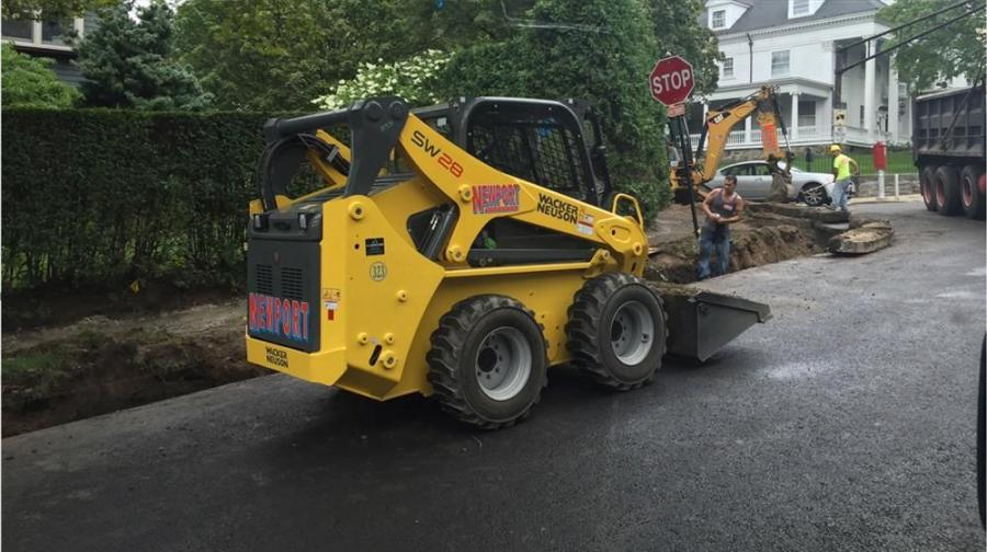 A Wacker Neuson skid steer assists a crew with transporting curb and providing gravel to backfill on the Fisher Avenue road reconstruction project in Brookline, Mass.