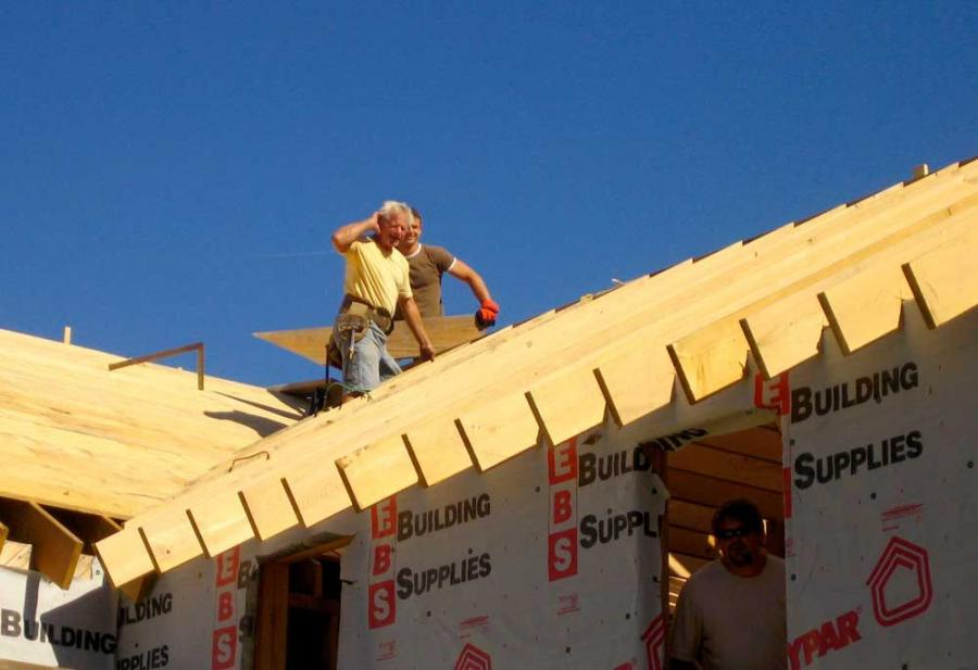 Mike Mangione and Father Luke Willenburg of St. Luke's Church, Barrington, R.I., help build the roof on the new farmhouse at H.O.M.E.