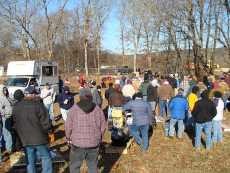 The crowd gathers to place the highest bid on the lots for sale.