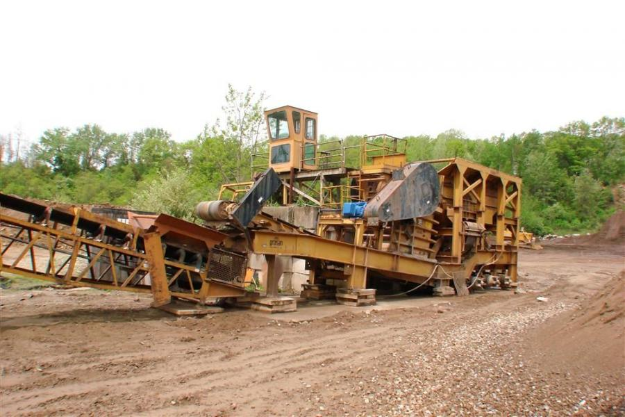 This Grasan portable jaw crusher plant, in operation since 1988, has been mounted on a concrete pad for stationary operation, with wheels removed for ease of maintenance.