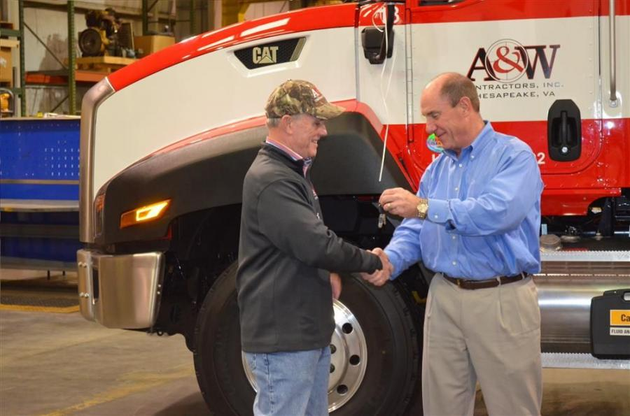 Jim Parker (R), CEO of Carter Machinery, presents the keys to James Archbell III, president of A & W Contractors.