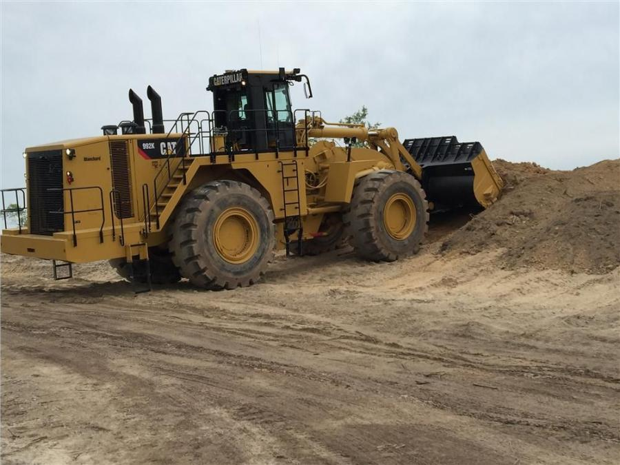The Cat 992K wheel loader equipped with a 15 cu. yd. bucket moves overburden material.