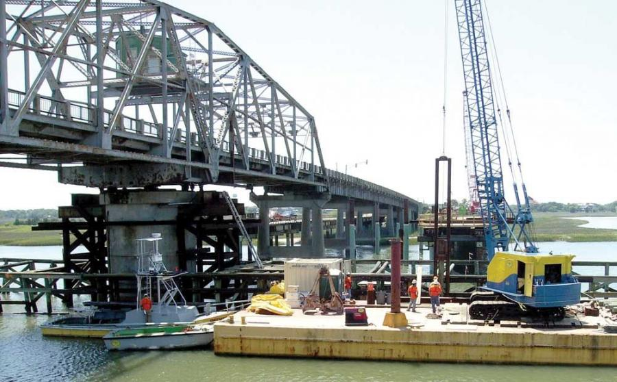 Photo courtesy of SCDOT and PCL Civil Constructors, Inc.  Subcontractor Freck Enterprises, Cocoa, Fla, is using a 50-ton (45 t) Bucyrus Erie 30 Super B crawler crane on a 30 by 120 ft. (9 by 36 m) barge to remove the existing timber piles, supports and de