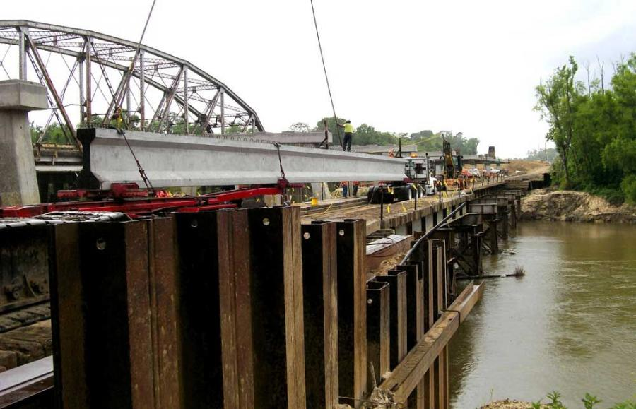 Setting precast girders using trestle while the Amite River is at flood stage.