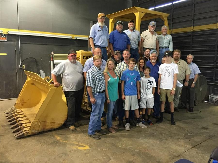 Standing with the company's first machine, a 1972 Cat 955K loader with 50,000 hours are Anthony Broome, Ironpeddlers Inc.; Amity Flowe-Broome; Isaak, Barrett, Noah, Tristen, LuAnn and Jimmy Flowe; and Keith Houseknecht, Kevin Stewart, Randy Carriker