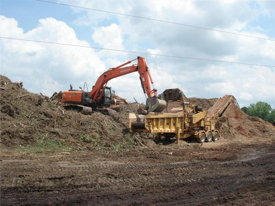 Elite Waste Services recently added a new Hitachi 210LC to its operation due to the reliability of the Hitachi excavators. The operator of the Hitachi loads tree debris into the Vermeer grinder.