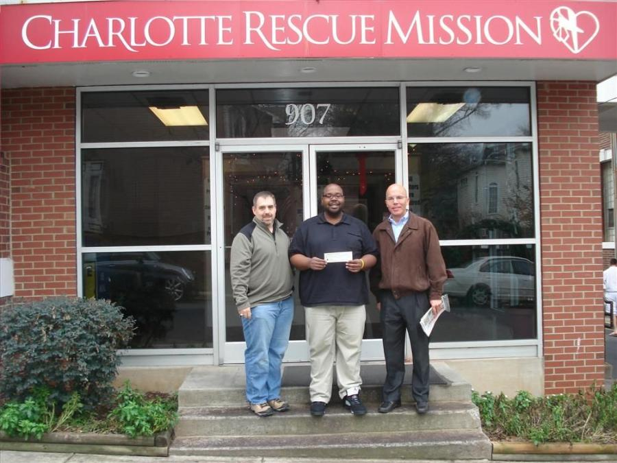 Terry Thomas (L), James River Equipment; and Richard McKeon (R), Construction Equipment Guide; present the $3,000 donation to Ed Boyce of the Charlotte Rescue Mission. The donation is from all of the construction equipment dealers in the Charlotte area.
