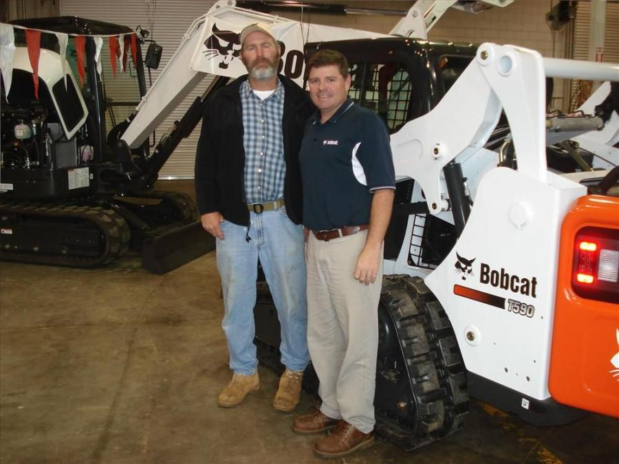 Paul Wigington (L) of Wigington Farms in Piedmont, S.C., listens to Jim Dills of Bobcat of Greenville discuss the Bobcat T590 track loader.