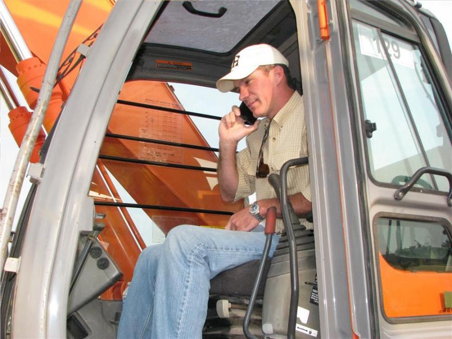 Brett Johnson of Vertical Earth, based in Cumming, Ga., makes a call in the cab of a Hitachi Zaxis 225 before the auction starts.