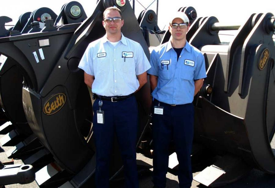 Justin Schultz (L) and Michael Fricchione, both in the operations group, stand in front of the Geith HDG 120 grapple.