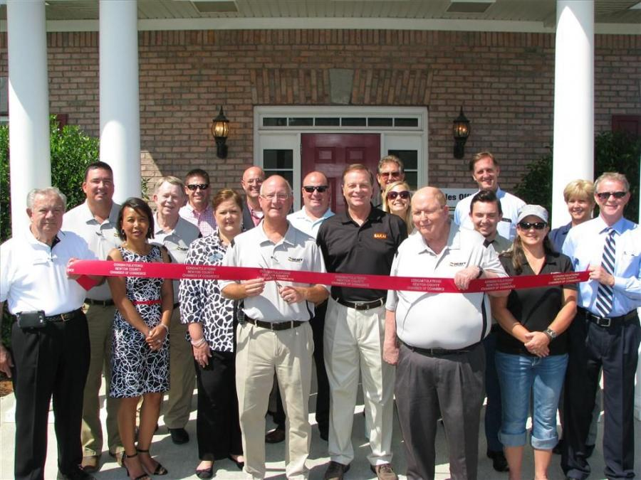 The Newton County Chamber of Commerce officially cuts the ribbon to commemorate the first day of business for the new Heavy Machines Inc. branch facility in Covington, Ga.