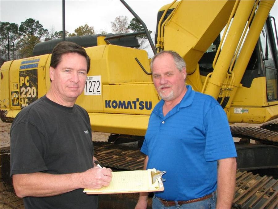 Doss Edwards (L) and Randy Thompson of Mid-State Equipment, Dublin, Ga., go over their notes on this Komatsu PC220LC excavator before heading to the bidding arena.