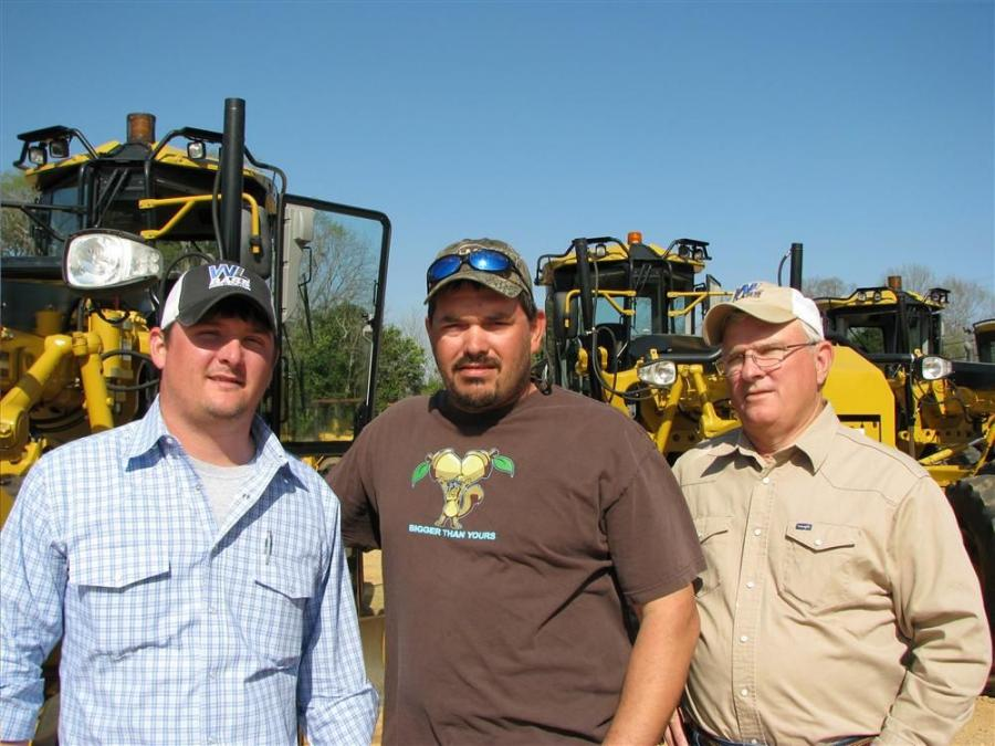 Admiring and inspecting a lineup of motorgraders in this sale (L-R) are Wes Bass, James Brewer and Mark Bass, all of W.L. Bass Construction, Monroe, La.